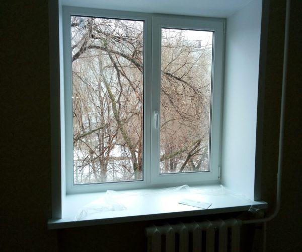 Окно в кирмичном доме с подоконником и откосами