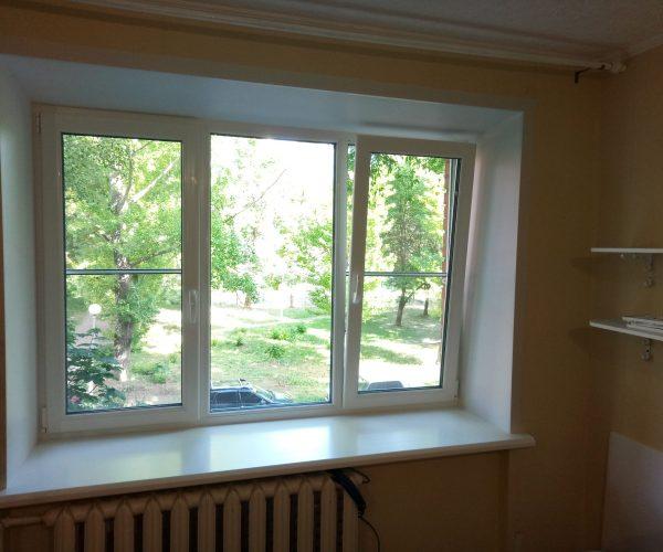 Трехстворчатое окно с двумя рабочими створками с отделкой, в кирпичном доме