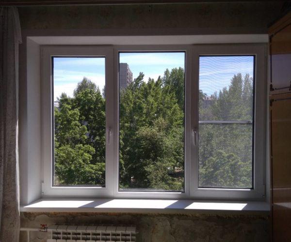 Трехстворчатое окно с двумя рабочими створками, с подоконником и откосами в панельном доме.